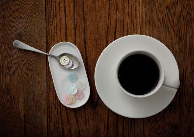 الأزرار البلاستيكية التي تزن 5 غرامات، أي ما يعادل كمية البلاستيك التي يمكن أن يأكلها شخص ما في أسبوع واحد، تُعرض مع فنجان من القهوة في هذا الرسم التوضيحي الذي تم التقاطه في طوكيو، اليابان 31 مارس 2020