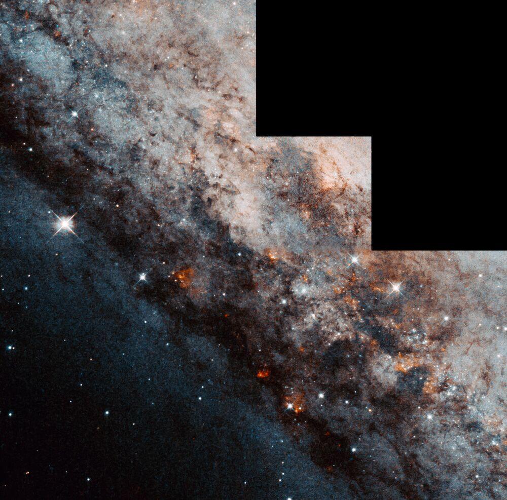 كالدويل 83، أو إن جي سي 4945، عبارة عن مجرة حلزونية ضلعية (مثل مجرتنا درب التبانة) تظهر على الحافة.