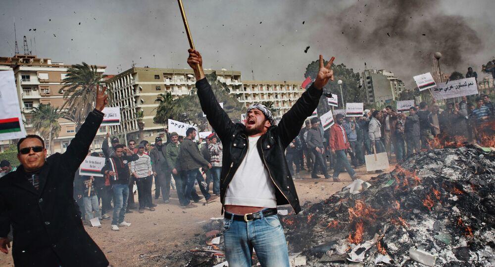 أهالي مدينة بنغازي يحرقون صور الزعيم الليبي معمر القذافي وملصقات مع اقتباساته و كتاب الأخضر من تأليفه، ليبيا 11 مارس 2011