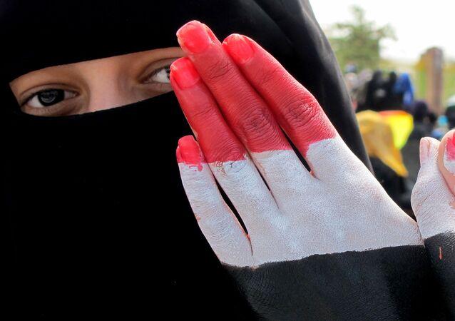 امرأة تظهر كفة يدها المرسوم عليها ألوان العلمين اليمني والسوري خلال مظاهرة حاشدة ضد حكم الرئيس علي عبد الله صالح في العاصمة اليمنية صنعاء، 4 نوفمبر 2011