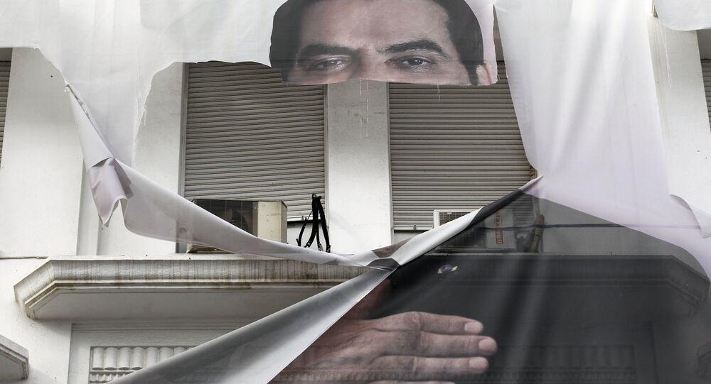 لافتة ممزقة للرئيس التونسي الأسبق زين العابدين بن علي وسط العاصمة تونس، 16 يناير 2011