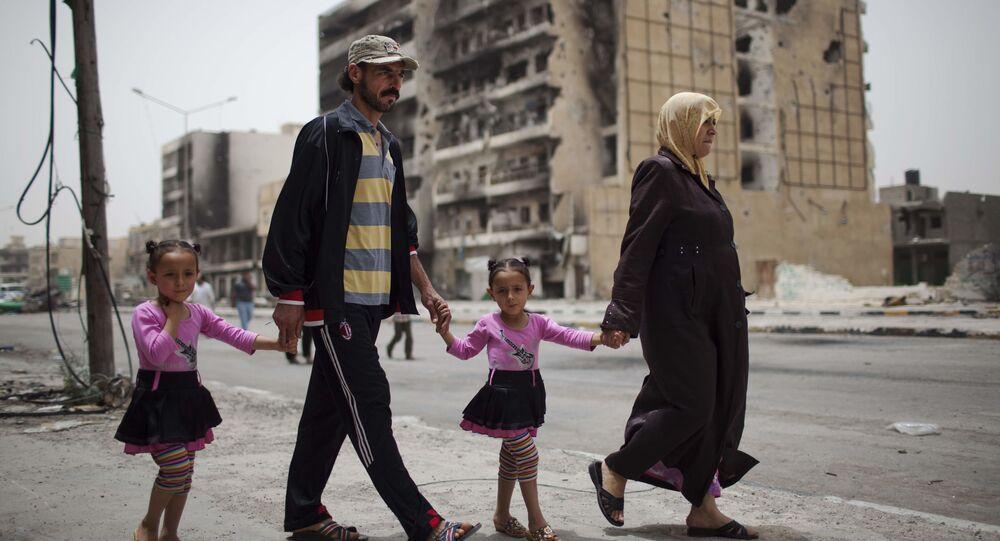 عائلة تسير في شارع طرابلس، مركز القتال بين قوات المعارضة الليبية وقوات معمر القذافي في مصراتة، 22 مايو 2011