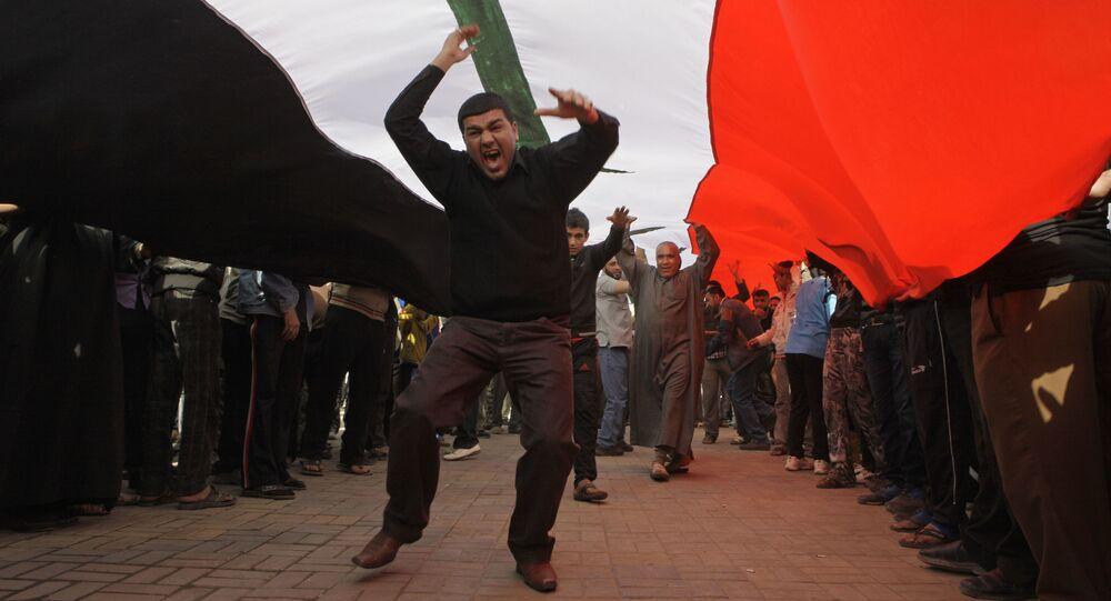 محتجون يهتفون بشعارات مناهضة للحكومة العراقية تحت علم عراقي ضخم، خلال مظاهرة في ساحة التحرير في بغداد، العراق  23 فبراير 2011