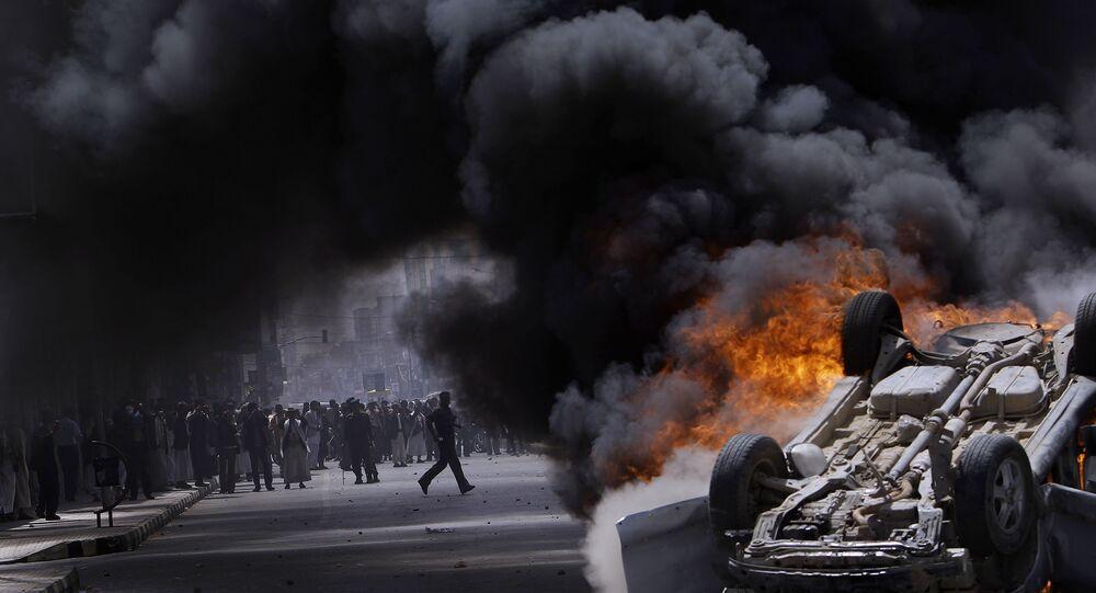 أنصار الحكومة اليمنية وراء دخان يتصاعد من سيارة مشتعلة تابعة لهم، التي أضرم فيها النار متظاهرون مناهضون للحكومة خلال اشتباكات في صنعاء، اليمن 22 فبراير 2011.
