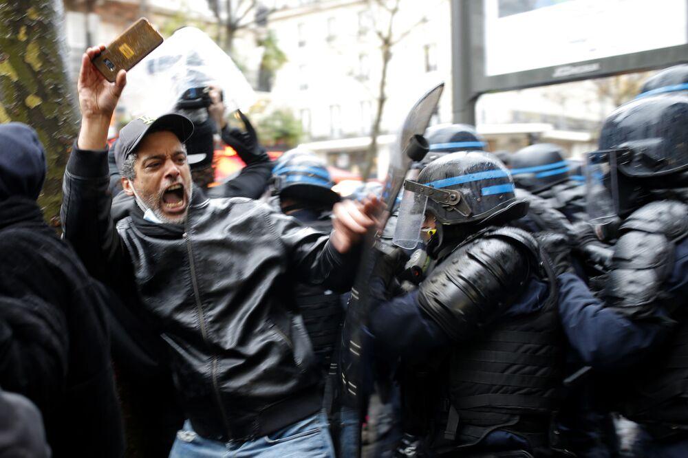 قوات الشرطة لمكافحة الشغب يقبضون على رجل كان يمسك هاتفه خلال الاحتجاجات، في باريس 12 ديسمبر 2020
