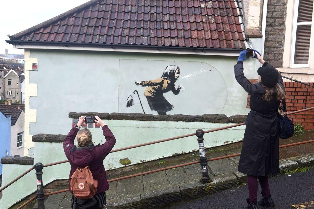 الناس يلتقطون صوراً لعمل فني جديد لبانكسي ظهر على جدار أحد شوارع  توترداون، بعنوان أتشو!!،  في بريستول، بريطانيا 11 ديسمبر 2020.