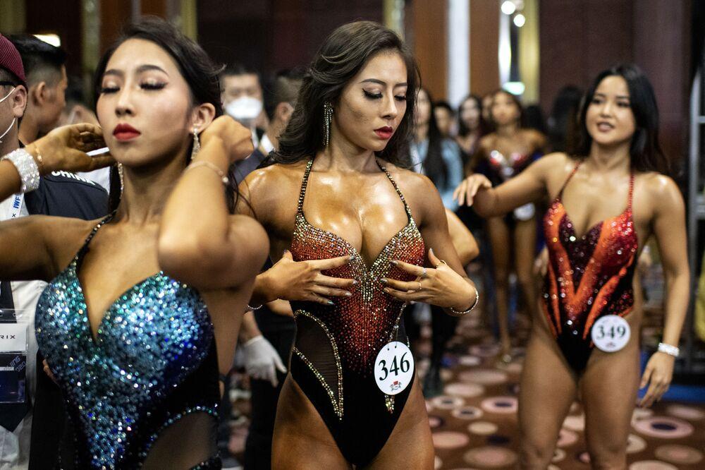 المشاركات في مسابقة كمال أجسام ينتظرن دورهن ليصعدن على خشبة المسرح خلال مسابقة بكين 2020 للاتحاد الدولي لرفع الأثقال (IWF) بكين 2020 في بكين في 11 ديسمبر 2020