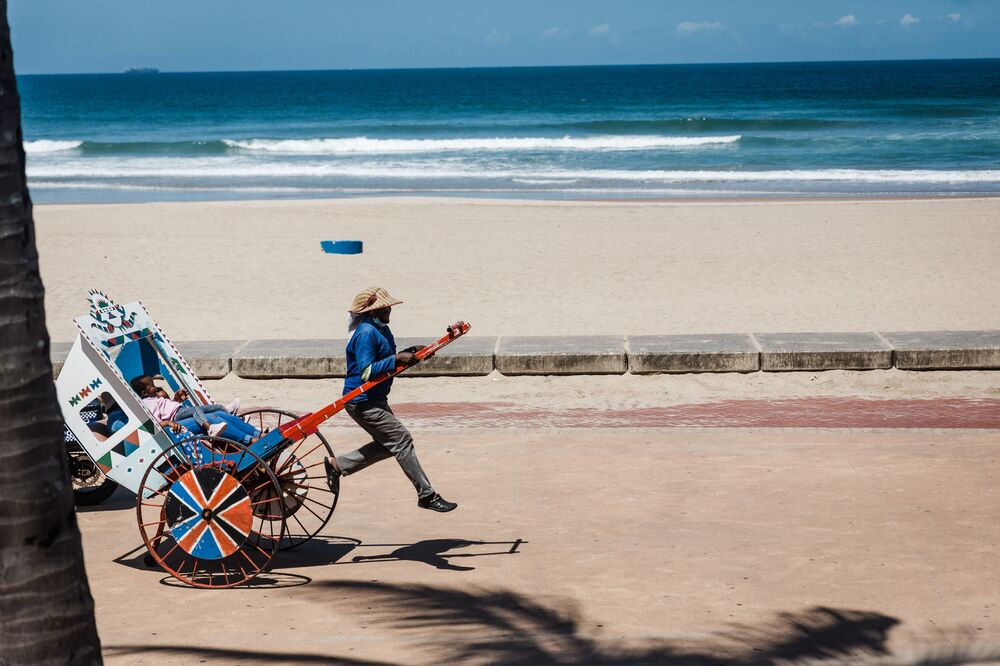 شخص يجر عربة السياح في رحلة على الشاطئ الشمالي في ديربان،  16 ديسمبر 2020، بعد أن فرضت حكومة جنوب أفريقيا قيودًا تمنع الجمهور من السباحة والتجمهر على الشاطئ بسبب الإعلان عن الموجة الثانية في 09 ديسمبر 2020.
