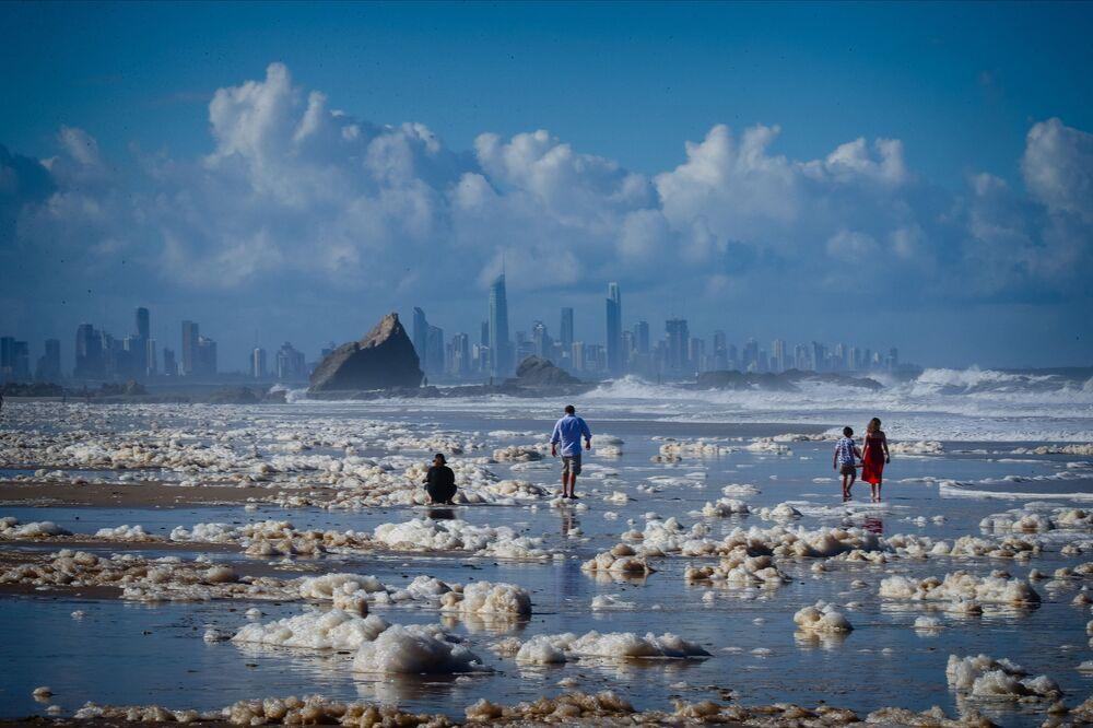يسير السائحون بين الرغوة المتكونة على الشاطئ في أعقاب إعصار على شاطئ كورومبين في 15 ديسمبر 2020، بعد أن اجتاح الطقس البري شمال نيو ساوث ويلز في أستراليا وجنوب شرق كوينزلاند مع هطول أمطار غزيرة ورياح قوية والمد الملكي هو المد الربيعى المرتفع.