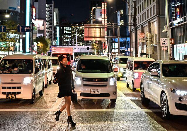 امرأة ترتدي كمامة تعبر شارعًا في طوكيو، اليابان 16 ديسمبر 2020