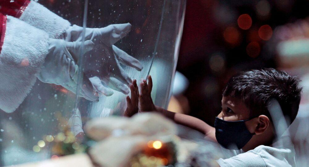 أبيليو دا كروز بينتو، 77 عامًا، يرتدي زي بابا نويل داخل فقاعة بلاستيكية، يحيي طفلًا في مركز تسوق وسط تفشي فيروس كورونا (كوفيد-19) في برازيليا، البرازيل، 15 ديسمبر 2020.