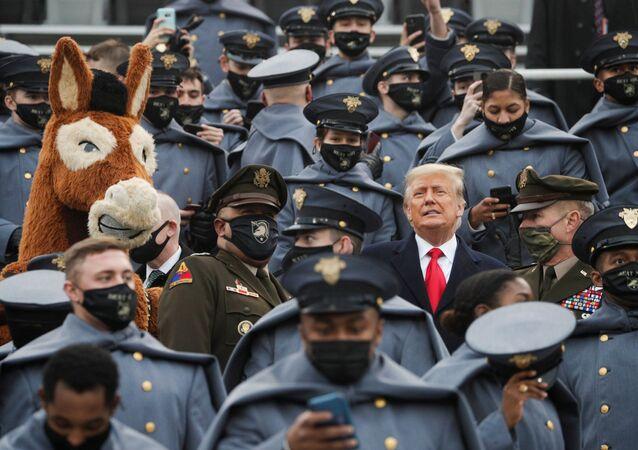 يقف الرئيس الأمريكي ترامب بين طلاب الجيش الأمريكي، أثناء حضوره مباراة كرة القدم الجماعية السنوية للجيش والبحرية في ملعب ميتشي  في ويست بوينت، نيويورك، الولايات المتحدة ، 12 ديسمبر 2020.