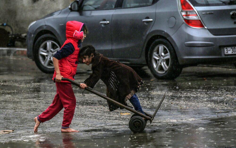 فتاة فلسطينية تدفع أخرى على عربة يدوية في يوم ممطر في مدينة رفح جنوب قطاع غزة، فلسطين 16 ديسمبر 2020