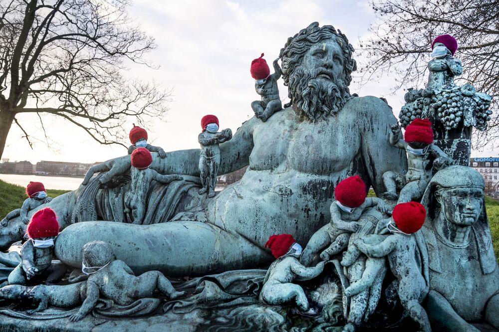 تماثيل برونزية صغيرة عند تمثال نيلين (النيل) في كوبنهاغن مغطاة بقبعات حمراء وكمامات صغيرة وسط أجواء الاستعداد بالاحتفال بالعيد الميلاد ورأس السنة وتفشي كورونا، الدنمارك 16 ديسمبر 2020