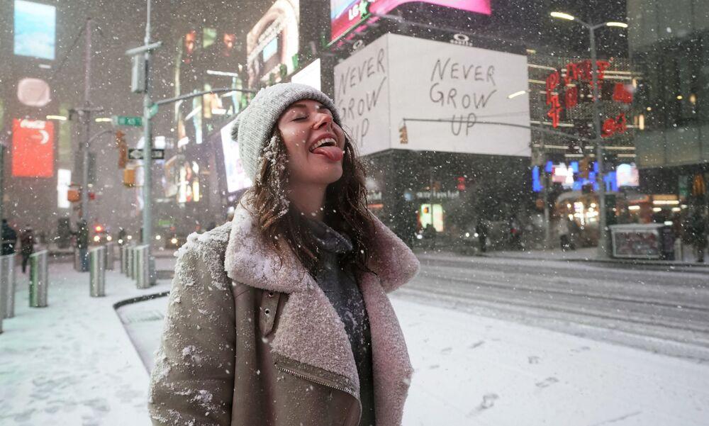 فتاة تقف وسط ميدان تايم سكوير في مدينة نيويورك، تلتقط حبات ثلج، إثر تساقط ثلوج كثيفة في المدينة، ديسمبر 17 ديسمبر 2020