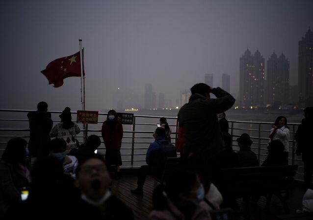 أشخاص يرتدون كمامات أثناء وحلة قارب سياحي على نهر يانغتسي، بعد عام تقريبًا من تفشي مرض فيروس كورونا (كوفيد-19) في ووهان، مقاطعة هوبي، الصين، 11 ديسمبر 2020.