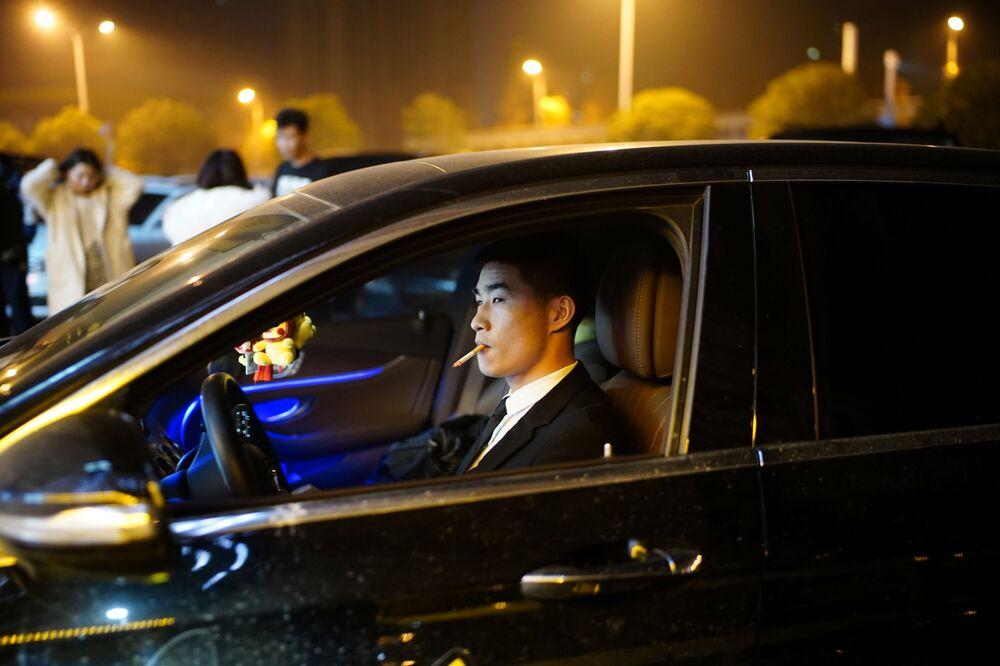 رجل يقود سيارة خارج ملهى ليلي، بعد عام تقريبًا من التفشي العالمي لمرض فيروس كورونا (كوفيد-19) في ووهان، مقاطعة هوبي، الصين، 12 ديسمبر 2020.