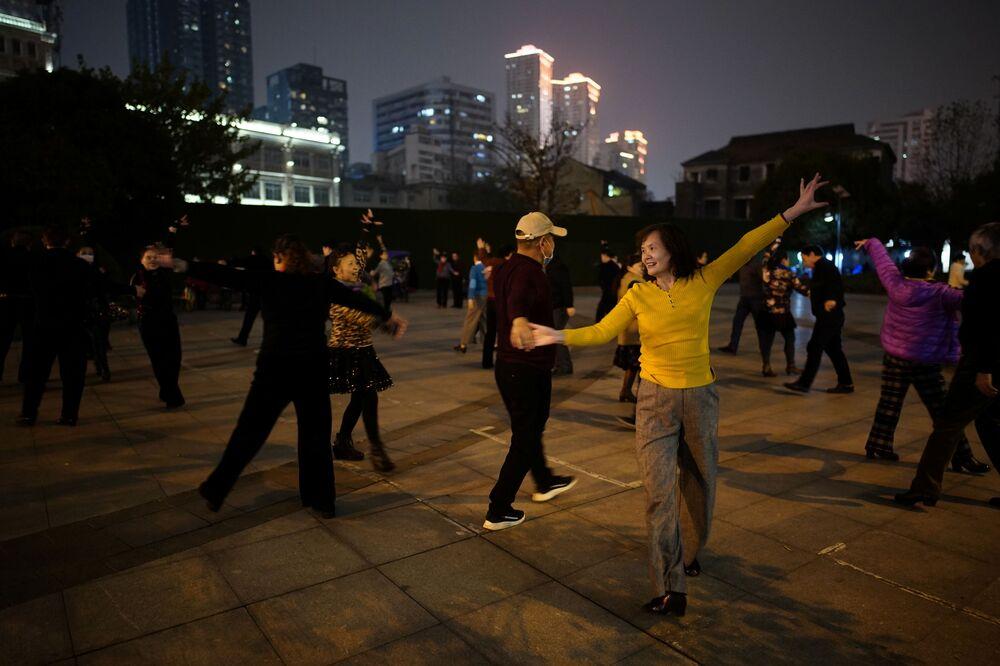 الناس يرقصون في حديقة عامة في الليل، بعد عام تقريبًا من تفشي مرض فيروس كورونا المستجد (كوفيد-19) في ووهان، مقاطعة هوبي، الصين، 11 ديسمبر 2020