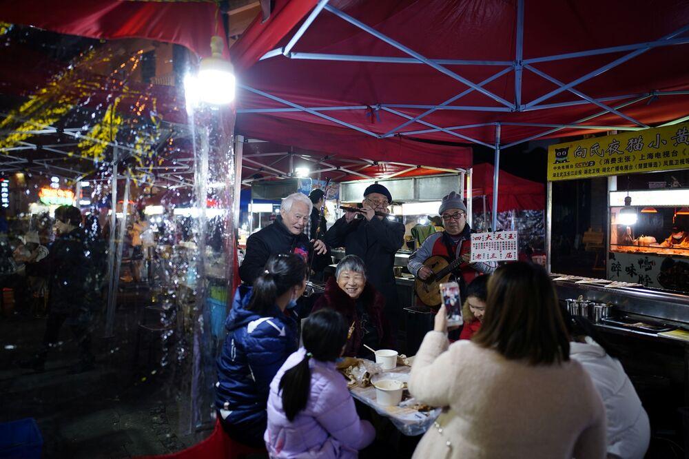 الناس يأكلون في مطعم في أحد شوارع المدينة ليلاً، بعد عام تقريبًا من تفشي مرض فيروس كورونا (كوفيد-19) في ووهان، مقاطعة هوبي، الصين 11 ديسمبر 2020