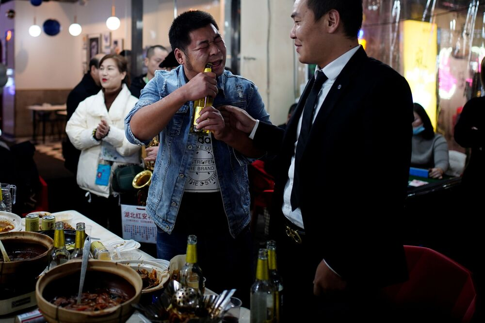 الناس في مطعم في أحد شوارع المدينة ليلاً، بعد عام تقريبًا من تفشي مرض فيروس كورونا (كوفيد-19) في ووهان، مقاطعة هوبي، الصين 11 ديسمبر 2020