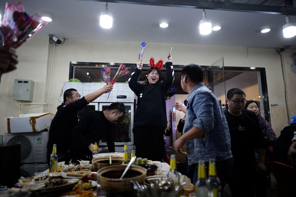 أشخاص يحتفلون بعيد ميلادهم في مطعم في أحد شوارع المدينة، بعد عام تقريبًا من تفشي مرض فيروس كورونا (كوفيد-19) في ووهان، مقاطعة هوبي، الصين 11 ديسمبر 2020