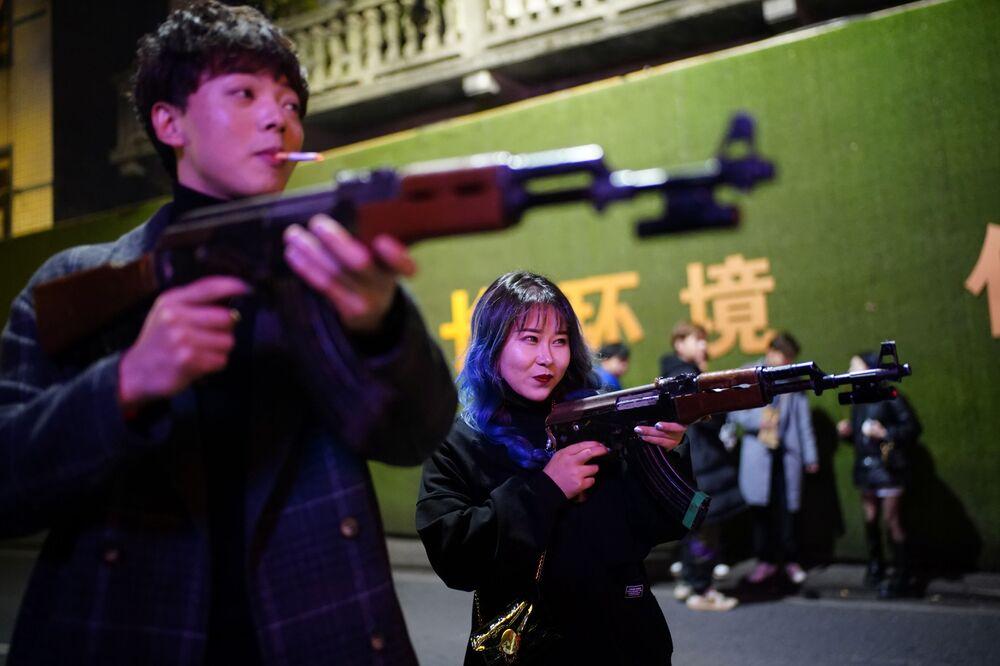 أشخاص يلعبون ببنادق الألعاب خارج نادي ليلي، بعد عام تقريبًا من تفشي مرض فيروس كورونا (كوفيد-19) في ووهان، مقاطعة هوبي، الصين 11 ديسمبر 2020