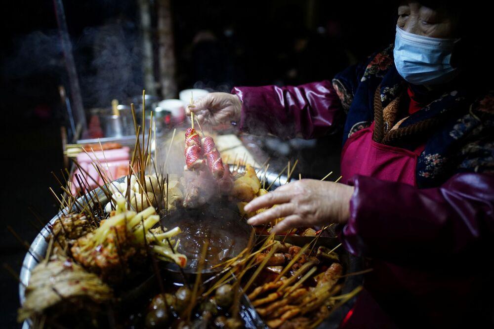 بيع وجبات خفيفة وسريعة في أحد شوارع ووهان، بعد عام تقريبًا من تفشي مرض فيروس كورونا (كوفيد-19)، مقاطعة هوبي، الصين 11 ديسمبر 2020