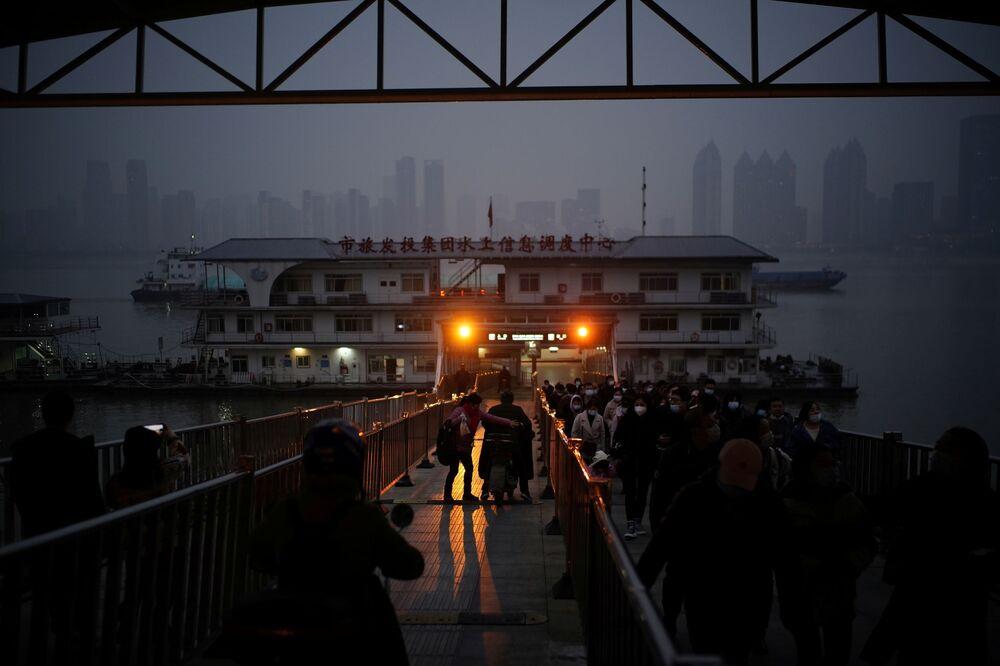 أشخاص يرتدون كمامات يخرجون من عبارة بعد عبورهم نهر انغتسي عند الغسق بعد عام تقريبًا من تفشي مرض فيروس كورونا (كوفيد-19)، مقاطعة هوبي، الصين 11 ديسمبر 2020