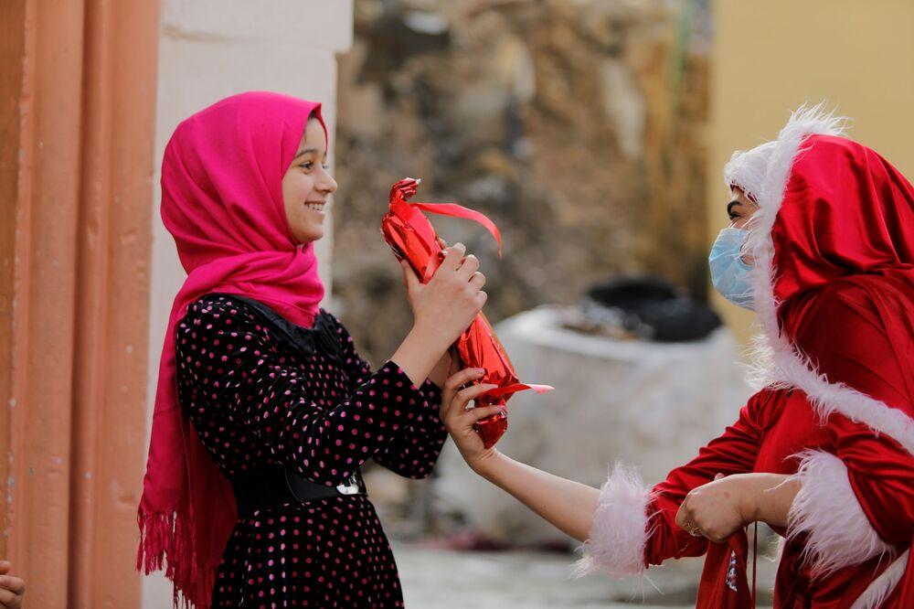 امرأة عراقية ترتدي زي بابا نويل وهي توزع الهدايا على أطفال مدينة الموصل القديمة، العراق 18 ديسمبر 2020