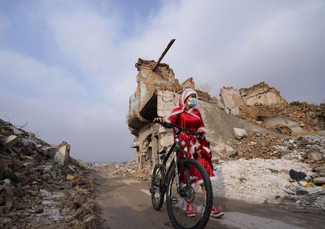 امرأة عراقية ترتدي زي بابا نويل وسط ركام المباني وهي تمشي بدراجتها وسط انتشار مرض فيروس كورونا (كوفيد-19)، في مدينة الموصل القديمة، العراق 18 ديسمبر 2020