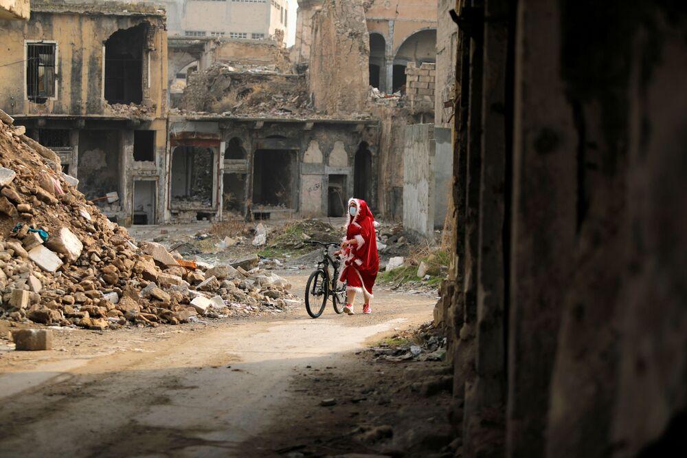امرأة عراقية ترتدي زي بابا نويل تنظر إلى المباني المدمرة وهي تمشي بدراجتها وسط انتشار مرض فيروس كورونا (كوفيد-19)، في مدينة الموصل القديمة، العراق 18 ديسمبر 2020