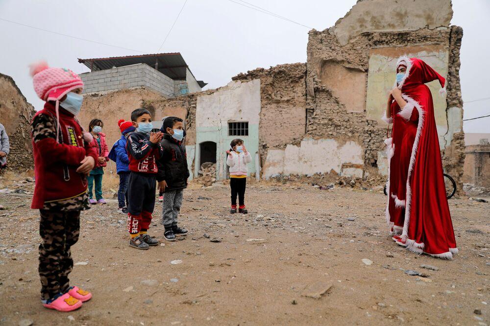 امرأة عراقية ترتدي زي بابا نويل وهي تلعب مع أطفال مدينة الموصل القديمة، العراق 18 ديسمبر 2020