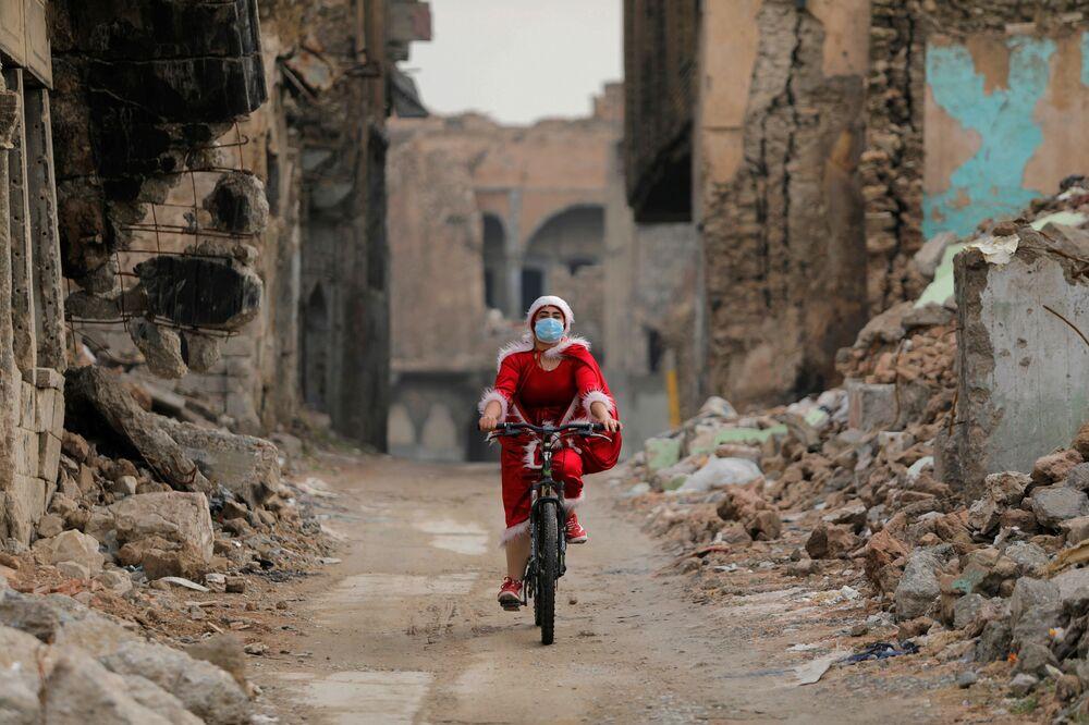 امرأة عراقية ترتدي زي بابا نويل وهي تركب دراجتها وسط انتشار مرض فيروس كورونا (كوفيد-19)، وسط ركام مدينة الموصل القديمة، العراق 18 ديسمبر 2020