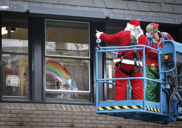 الوضع في بريطانيا مع ظهور سلالة كورونا الجديدة - رجال يرتدون زي بابا نويل ويحيون مرضى مستشفى ليدز للأطفال، إنجلترا 21 ديسمبر 2020