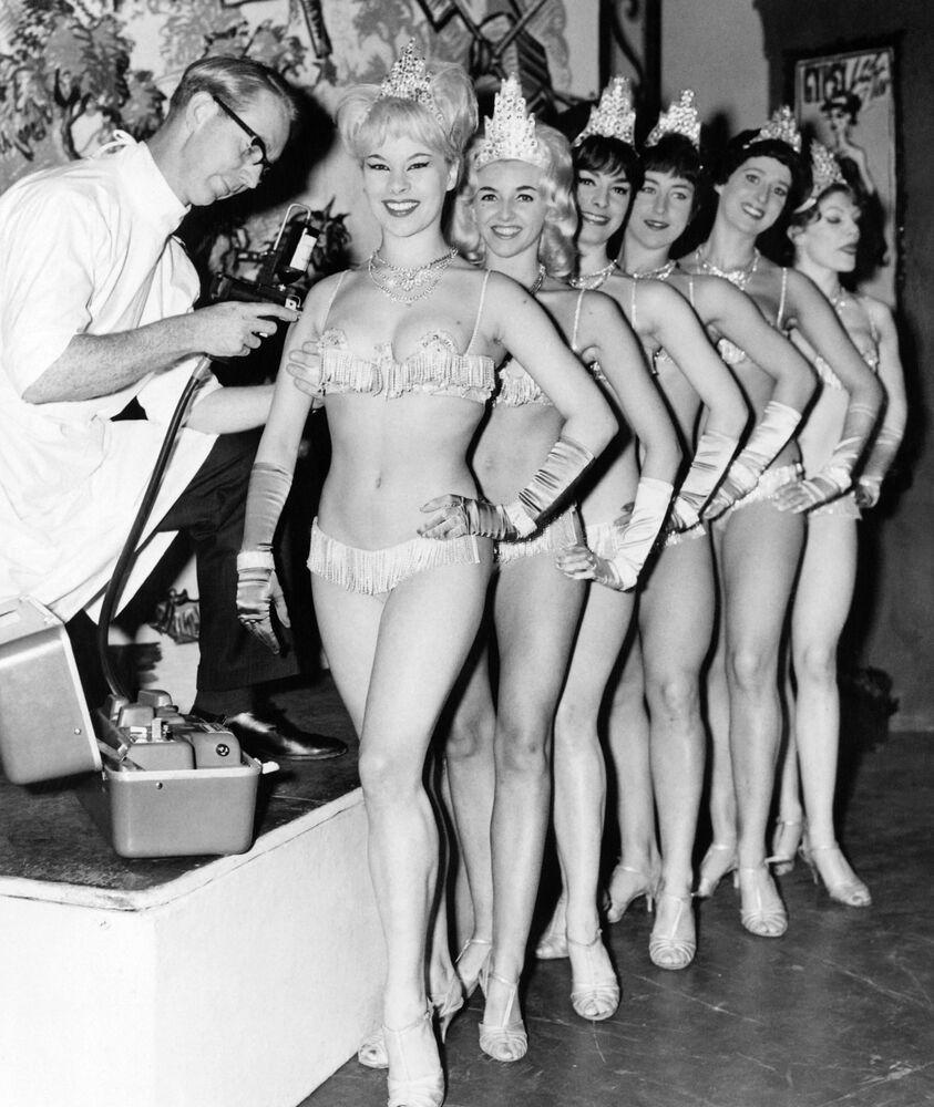 فتيات الاستعراض المسرحي ويندميل غيرلز (The Windmill Girls) من مسرح  ويندميل في لندن، أثناء تطعيمهن بلقاح ضد الإنفلونزا، 12 سبتمبر 1963.