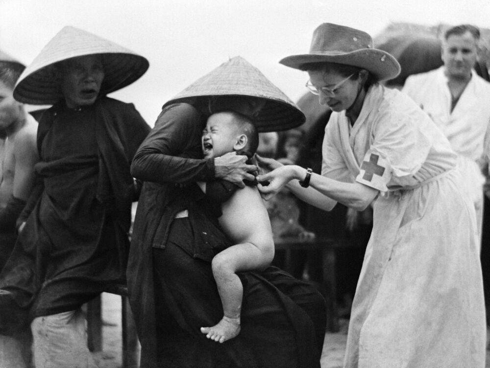 ماري جوزيت فرانكو (يمين) ، ممرضة استعمارية، أثناء تلقيح طفل ضد الكوليرا في مونغ دوك، الهند الصينية،  10 أكتوبر 1953