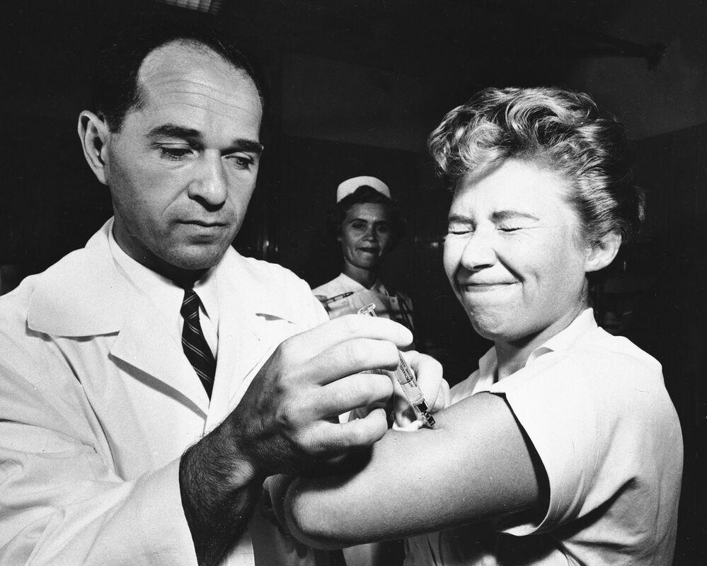 تظهر هذه الصورة الارشيفية التي التقطت في 16 أغسطس 1957، الدكتور جوزيف بالينجر وهو يعطي مارجوري هيل، الممرضة في مستشفى مونتيفيوري في نيويورك، أول لقاح مضاد للأنفلونزا الأسيوية (جائحة  1957-1958) يتم إعطاؤه في مدينة نيويورك الأمريكية.