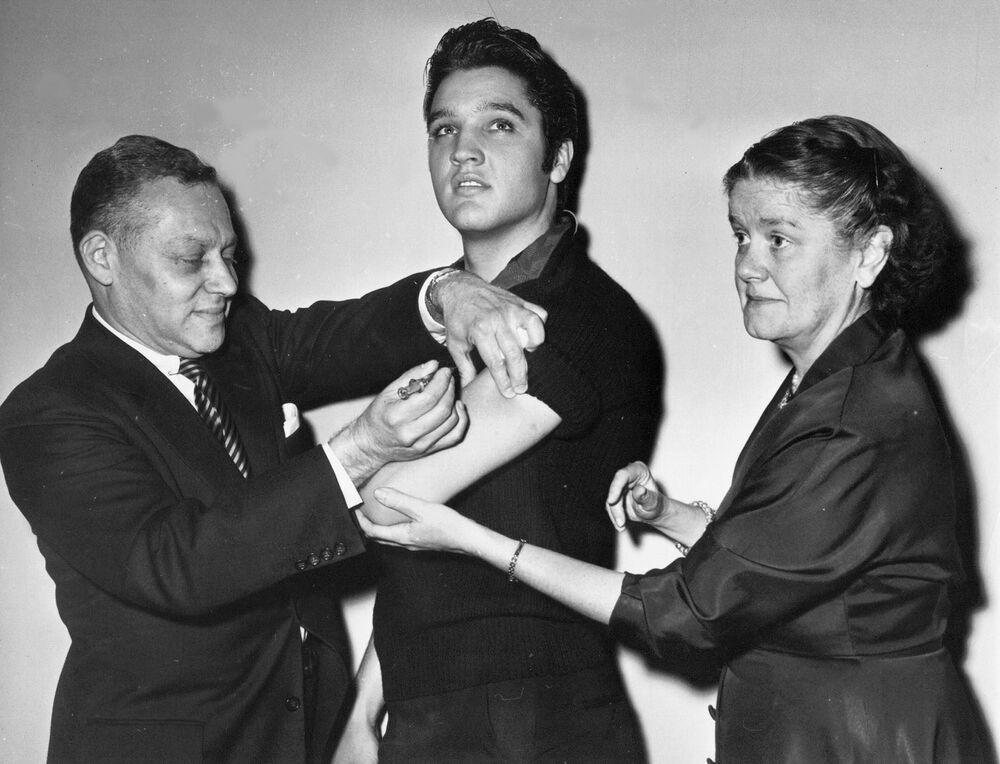في هذه الصورة الأرشيفية التي تعود إلى 28 أكتوبر 1956، يتلقى الفنان الأمريكي الشهير إلفيس بريسلي لقاح ضد شلل الأطفال في مدينة نيويورك، من قبل الدكتور هارولد فورست (يسار الصورة)، والدكتورة ليونا بومغارتنر (يمين)، مفوضة دائرة الصحة في مدينة نيويورك الأمريكية.