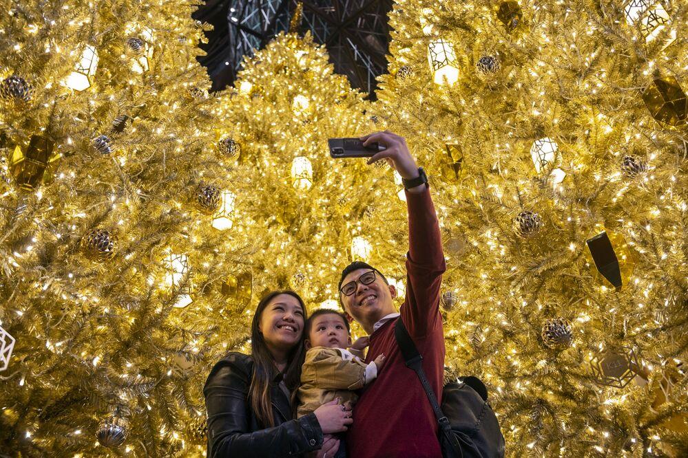 زوجان مع طفلهما يلتقطان صورة سلفي على خلفية أشجار عيد الميلاد الذهبية في أحد مراكز التسوق التجارية في هونغ كونغ، 19 ديسمبر 2020