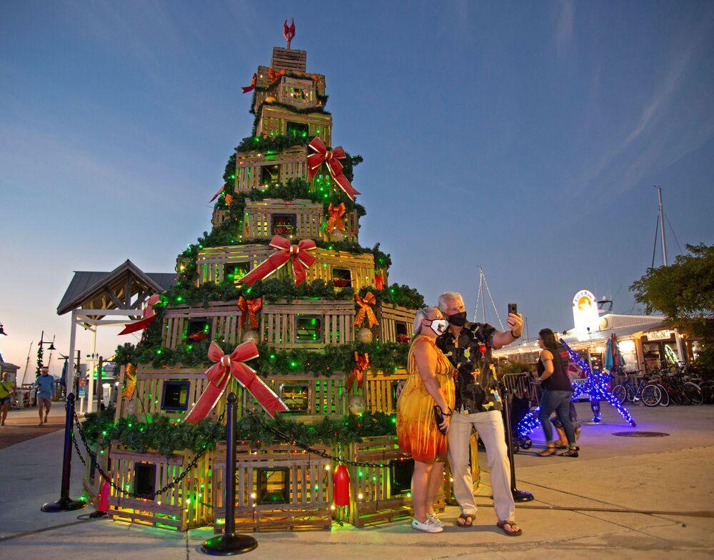 شخصان يقفان لالتقاط صورة سيلفي أمام شجرة عيد الميلاد مصنوعة من صناديق تستعمل في صيد سرطان البحر في كي ويست، فلوريدا، الولايات المتحدة، 13 ديسمبر 2020