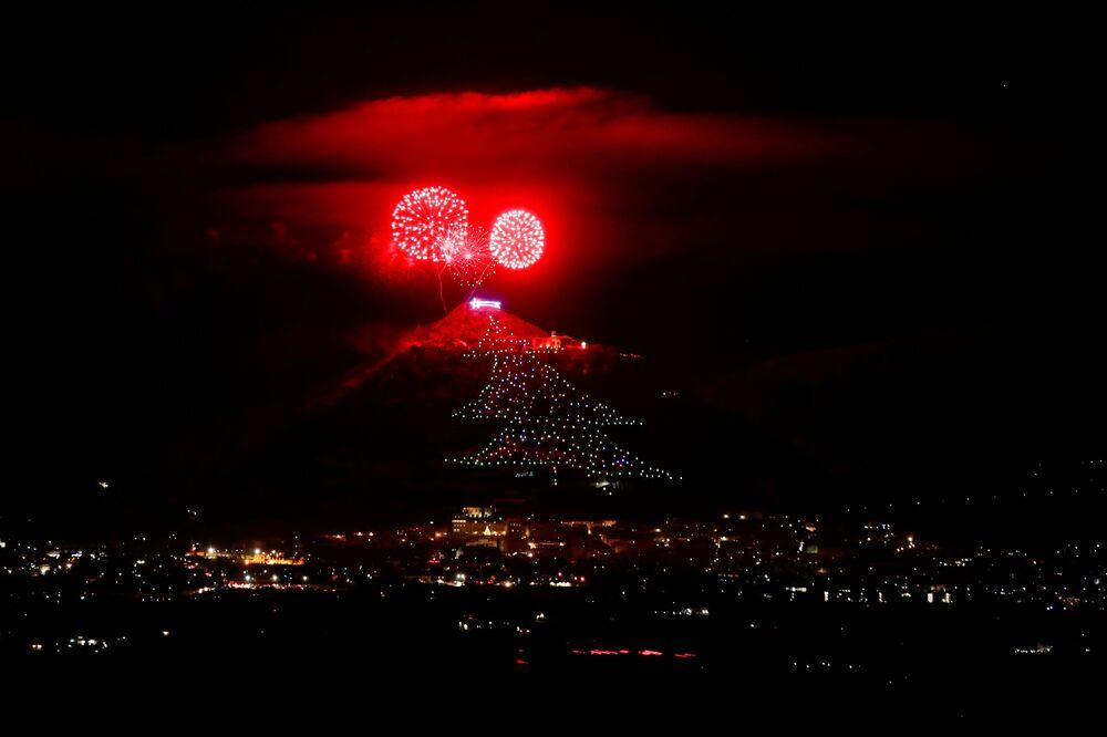 الألعاب النارية على خلفية إضاءة أكبر شجرة عيد الميلاد في العالم على منحدر جبل إنجينو في مدينة غوبيو التي تعود إلى القرون الوسطى بإيطاليا، 7 ديسمبر 2020