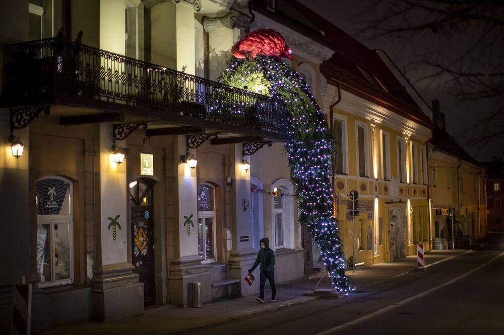 رجل يسير أمام شجرة عيد الميلاد تنحدر من شرفة مبنى في مدينة فيلنيوس، ليتوانيا، 8 ديسمبر 2020