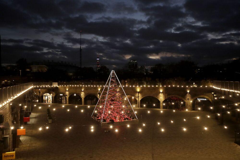شجرة عيد ميلاد في حوض ضمن الزينة غير التقليدية هذا العام في ساحة كول دروبز يارد، والتي تشكل جزءًا من حي  كينغز كروس، في لندن، مضاءة أثناء الإغلاق الثاني لفيروس كورونا في إنجلترا، 23 نوفمبر 2020