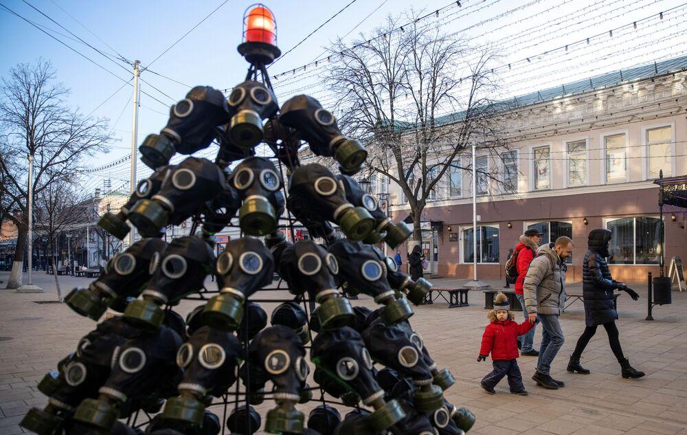 أشخاص يسيرون بجوار شجرة عيد الميلاد المصنوعة من الأقنعة الواقية من الغازات في مدينة ريازان، روسيا، 12 ديسمبر 2020