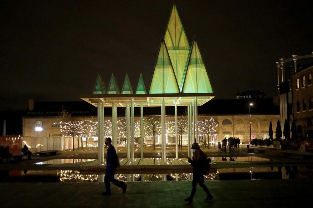 يمشي أشخاص يرتدون كمامات الوجه أمام شجرة نيميتون الكهربائية في ساحة غراناري، التي صممها مركز التصميم المعماري المحلي سام جاكوب استوديو، والذي يشكل جزءًا من حي كينغز كروس ضمن منشآت زينة عيد الميلاد غير التقليدية في لندن، خلال ثاني إغلاق لفيروس كورونا في إنجلترا، 23 نوفمبر 2020