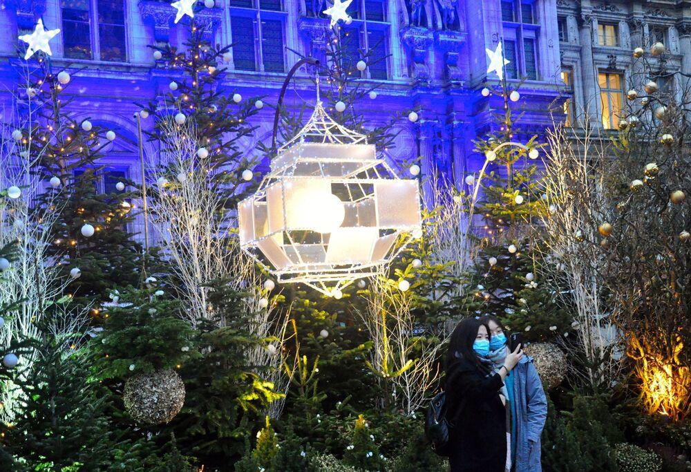 سياح يلتقطون صور سيلفي على خلفية أشجار غيد الميلاد بالقرب من قاعة مدينة فندق أوتيل دي فيل في باريس، فرنسا  21ديسمبر 2020