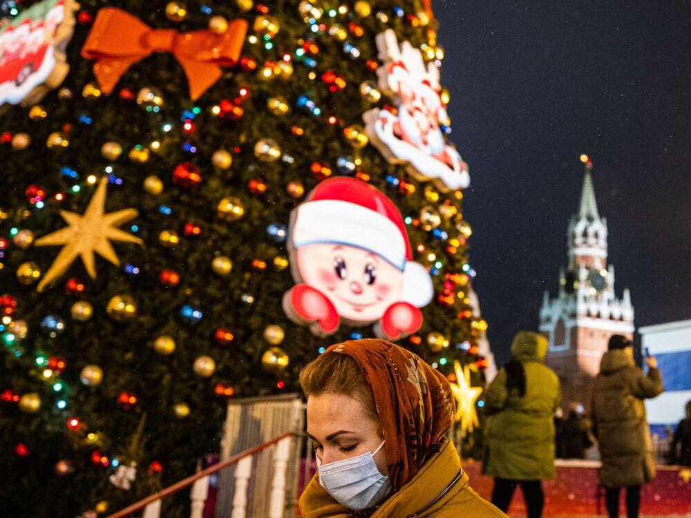 امرأة ترتدي كمامة وهي تسير بجوار شجرة عيد الميلاد في الساحة الحمراء وسط موسكو، 1 ديسمبر 2020