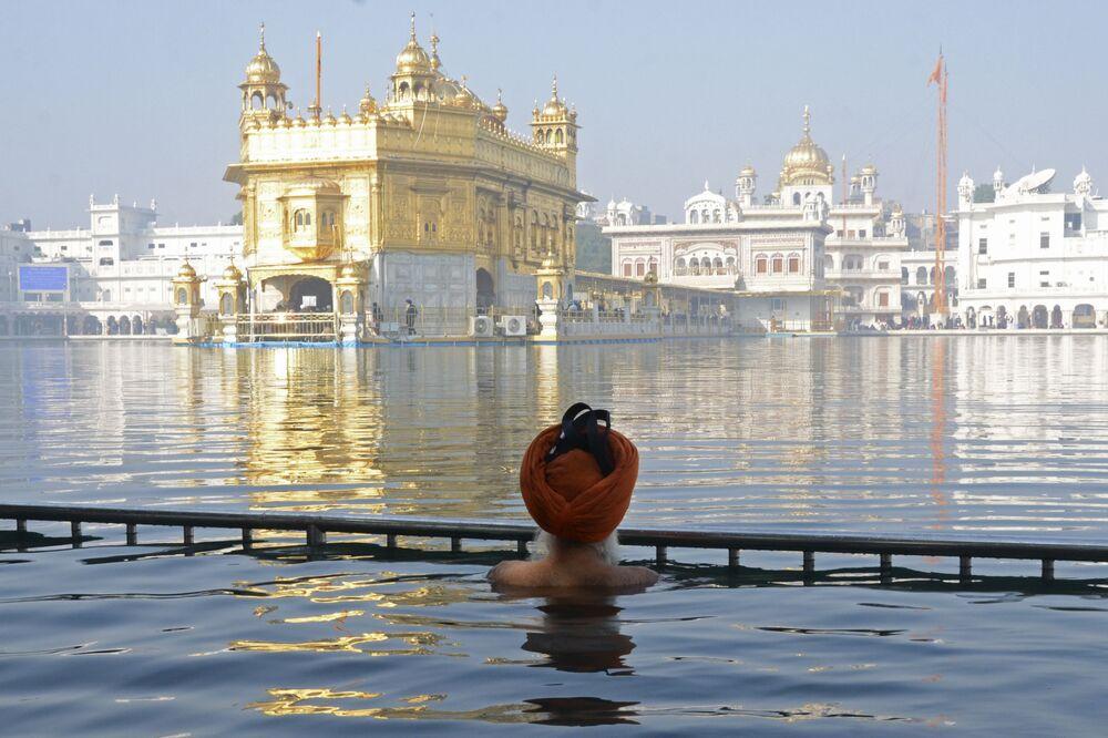 أحد المخلصين السيخيين يغطس في مياه ساروفار المقدسة التابعة للمعبد الذهبي في يوم استشهاد السيخ غورو تيغه بهادور التاسع، في أمريتسار، الهند 19 ديسمبر 2020