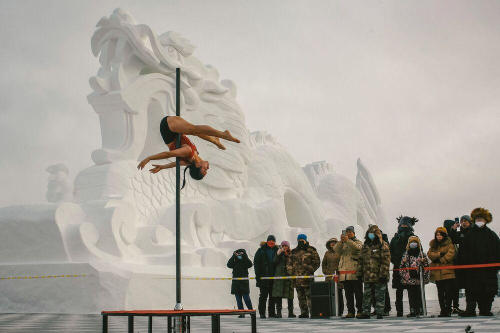 أشخاص يشاهدون عازفًا خلال مسابقة للرقص على العمود وسط درجات حرارة تقل عن 30 درجة تحت الصفر في موهي بمقاطعة هينغلونغ جيانغ بشمال شرق الصين، 21 ديسمبر 2020