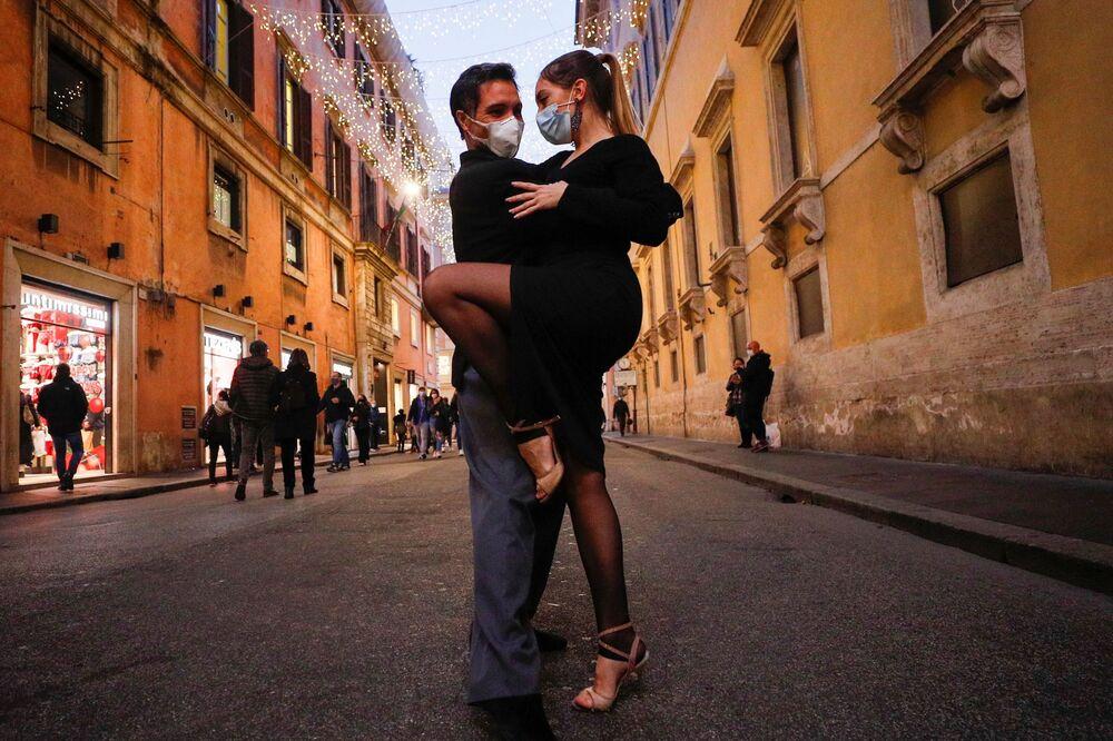 شخصان يرقصان التانغو في أحد شوارع مدينة روما، قبل يوم واحد من عودة إيطاليا إلى الإغلاق العام خلال فترة عيد الميلاد كجزء من الاجراءات الاحترازية للحد من انتشار مرض فيروس كورونا (كوفيد-19)، 23 ديسمبر 2020 .